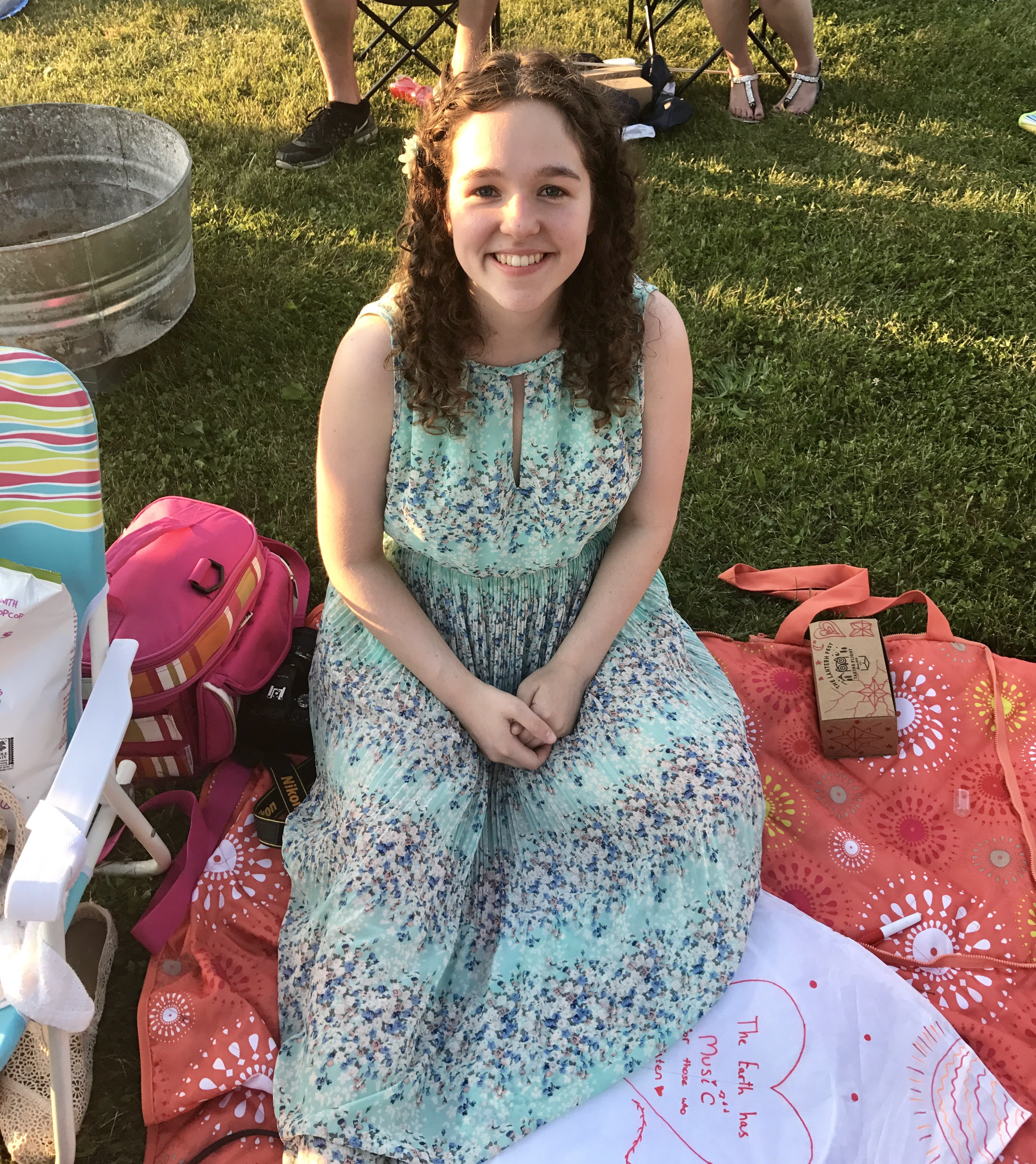 Student Ashley Myers relaxes on a picnic blanket.